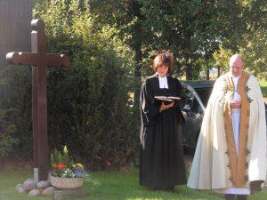 Pfarrerin Ingeborg Dahl und Pfarrer Hermann Josef Zeyen segnen das Kreuz